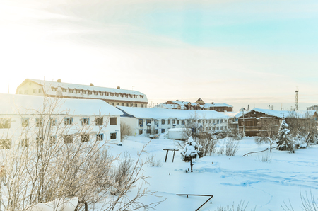 Winter in the Northern hinterland on the background of barracks bright sun and frost