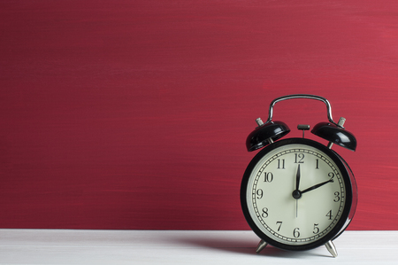 Still life, Retro black clock on white table and red grunge background.