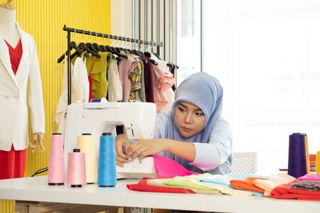 A young Asian Muslim woman designer as a startup business owner is using sewing machine on working table in her tailor shop.