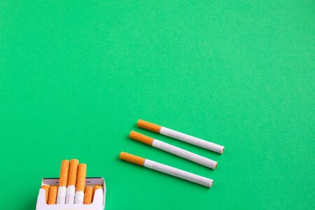 three loose cigarettes next to a pack on green table Stockfoto
