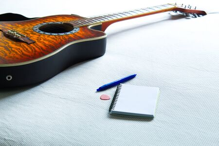 acoustic guitar on bed next to notebook and pen to compose songs Foto de archivo