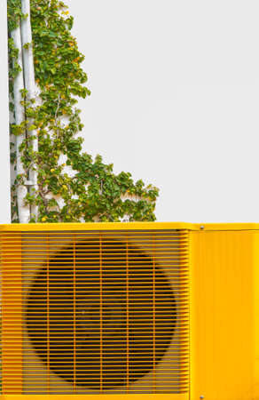 expel: The yellow  air conditioning wall-mounted  outside the building  Stock Photo