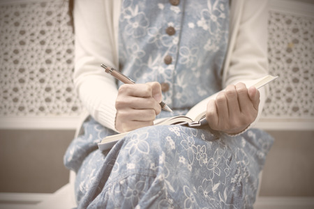 Close-up of a young girl writing into her diary, in the park - Soft focus photo