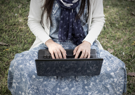 A young girl using laptop in park - Soft focus photo
