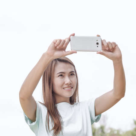 camera phone: Sofe focus. Pretty young woman taking picture with camera phone.