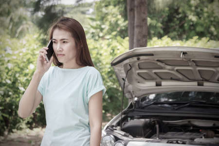 calling for help: Young woman with broken car calling for help Stock Photo