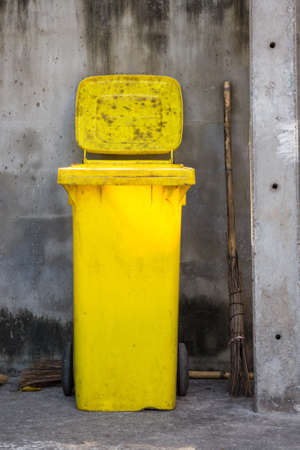 public service: Yellow plastic bin against a stone wall Stock Photo