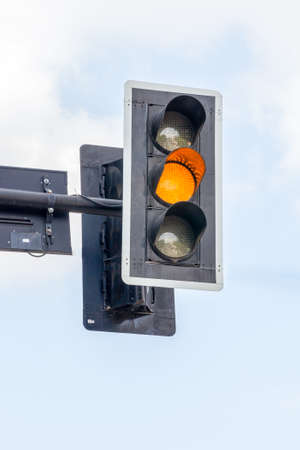 amber light: Amber color on the traffic light with blue sky in background