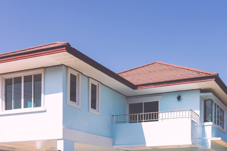 proprietary: house roof, sunny blue sky background Stock Photo