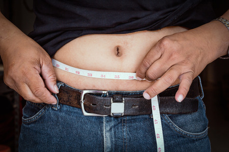 overeat: big belly of a fat man and measuring tape Stock Photo