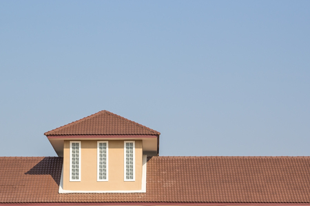 window repair: building a new roof of home, blue sky as background Stock Photo