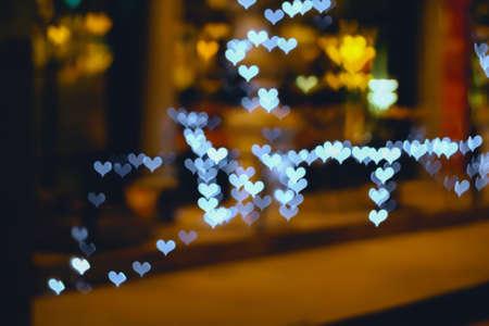 burnish: Colorful hearts bokeh on a dark background, white heart bokeh.