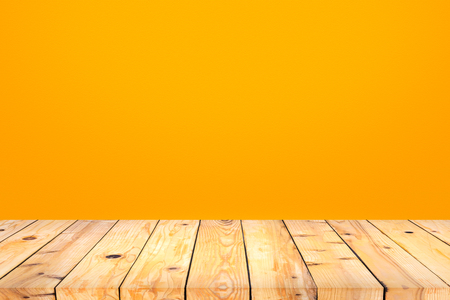 countertop: Wood table top on orange wall background Stock Photo