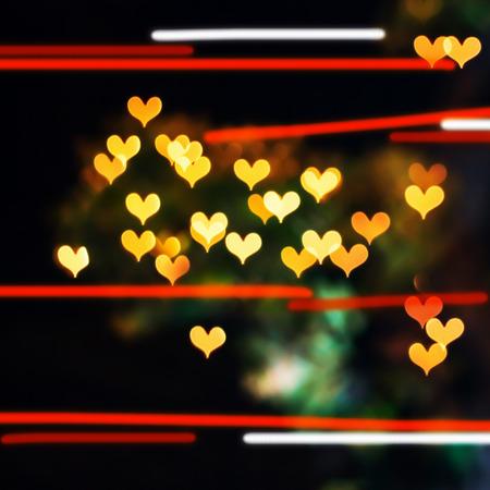 burnish: Colorful hearts bokeh on a dark background, orange heart bokeh.