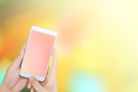woman hand holding a smartphone on abstract blurred background.