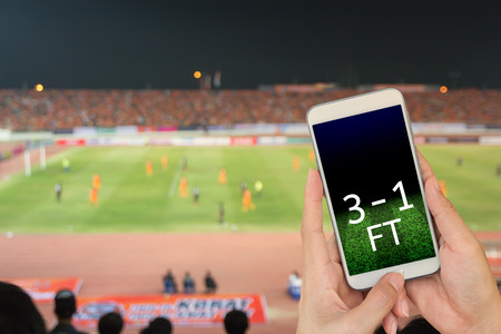 Hand holding mobile smart phone with score on black screen, blur image of a football field as background.