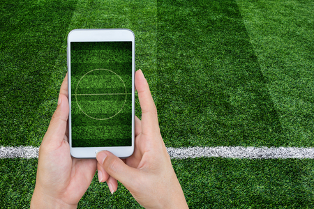 Hand holding mobile smart phone with football stadium, image of a football field as background. Stock Photo