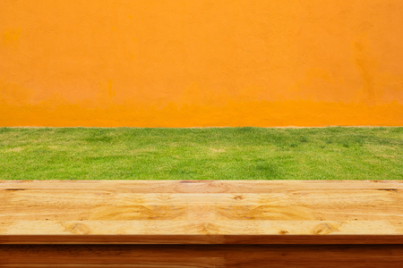 Empty wooden table with green grass and orange wall background. For display or montage your products