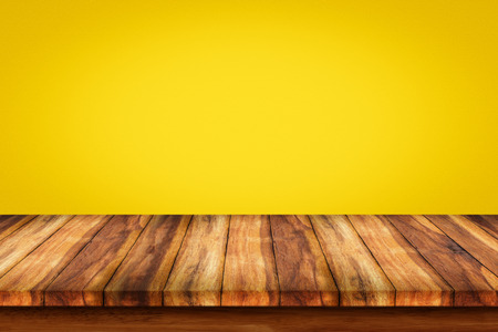 countertop: Empty wooden table with yellow gradient wall background. For display or montage your products. Stock Photo