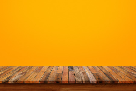 Wood table top on orange wall background Stock Photo