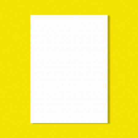 sheet of paper: Abstract white paper sheet on yellow wall background. Stock Photo
