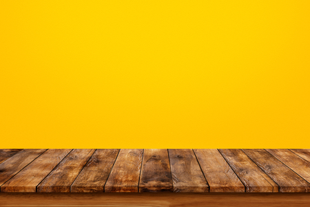 table top: Wood table top on orange wall background Stock Photo