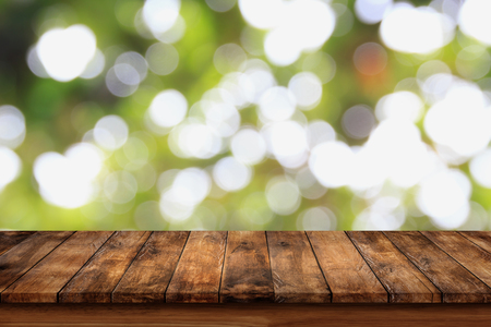 Empty wooden table with bokeh abstract green background. For display or montage your products. Stock Photo