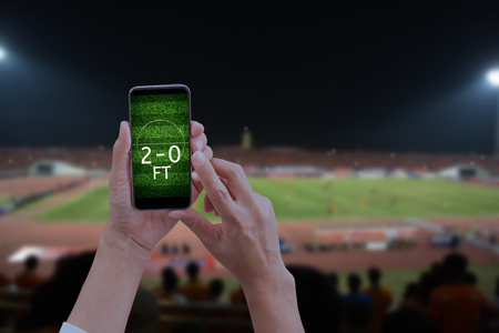 Hand holding mobile smart phone with football field, blur image of a soccer field as background. Stock Photo