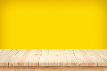 wood table: Wood table top on yellow wall background.