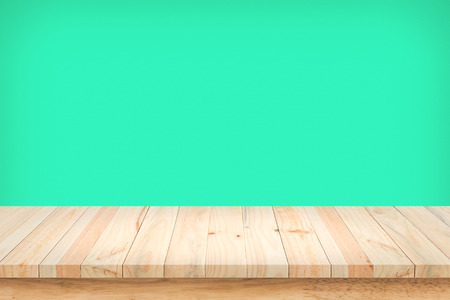 countertop: Wood table top on green wall background. Stock Photo