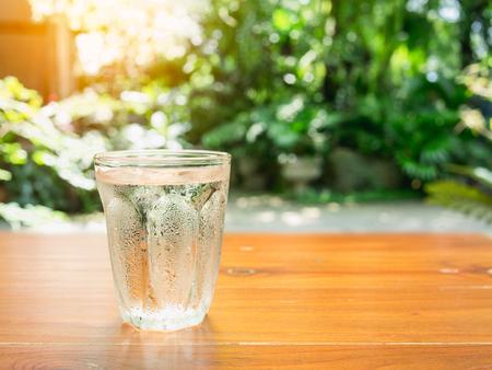 ボケ味、自然の背景の木のテーブルの上の水のガラス。