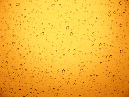 water drops on yellow metal texture background.