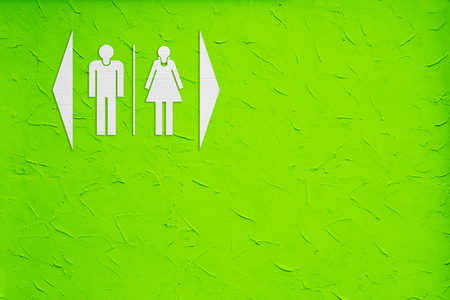 gents: White toilet sign on green wall background.