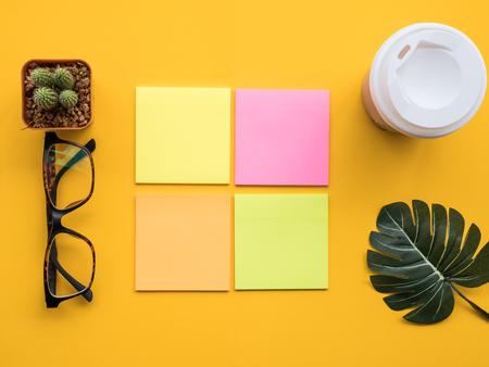 Entwerfen Sie flaches Lagebild des Arbeitsplatzschreibtischs mit Post-It, heißem Kaffee, Kaktus, Blatt und Gläsern auf gelbem Hintergrund. Standard-Bild - 89058401