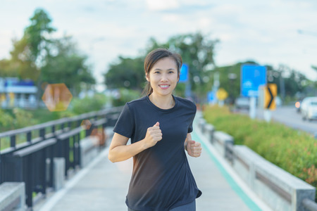 Young woman jogging on street background.