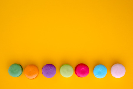 Colorful macarons on yellow background Stock Photo