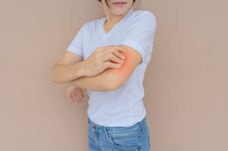 Woman scratching her hand on brown wall background.