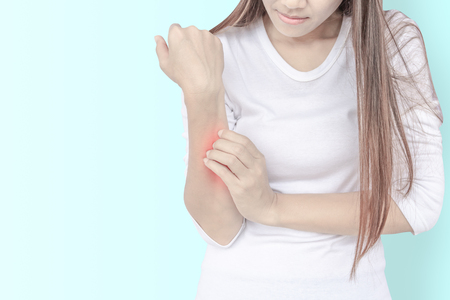 Jeune femme se grattant le bras qui démange sur fond de mur. Problème de peau. Banque d'images