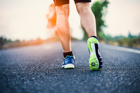 Athlete runner feet running on road, closeup on shoe.