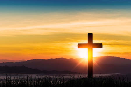 Silhouette of cross on mountain sunset background. Фото со стока