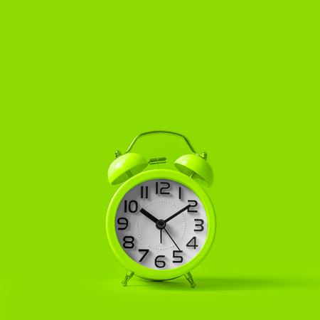 Green vintage alarm clock on green background.