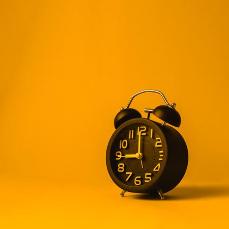 Black vintage alarm clock on yellow background.