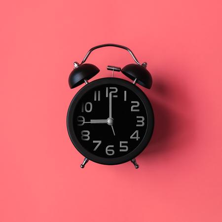 Black vintage alarm clock on pink background. Banco de Imagens