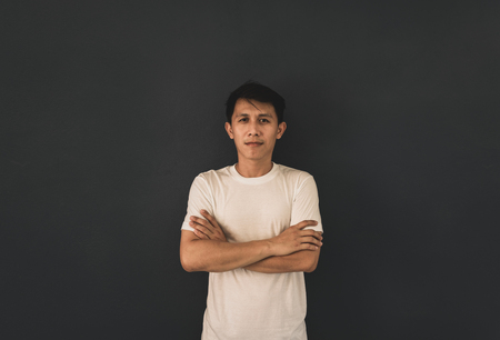 Asian guy in white blank t-shirt on black wall background.