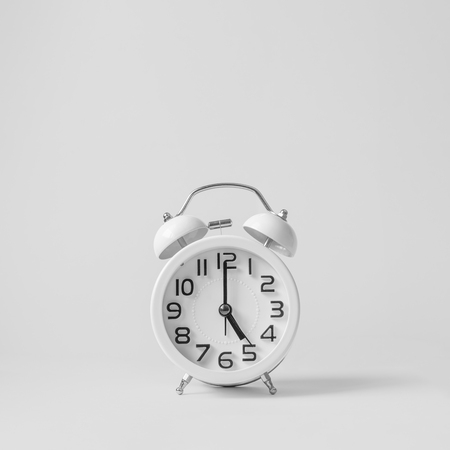 White vintage alarm clock on white background. Concept  get off work at five. Фото со стока - 122874643