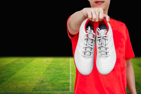 Man holding white football boots in his hand on soccer field.