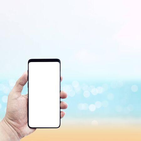 Mans hand holding smartphone with blur sea in sammer background.