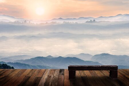 Old wood chair with beautiful foggy winter sunrise in mountains natural background. Stockfoto