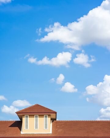 Roof of a detached house with blue sky and clouds background. Stock Photo