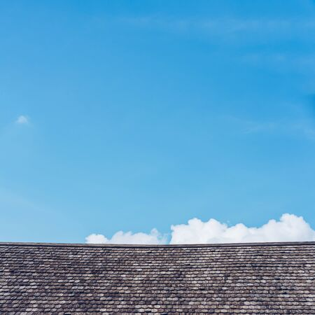 Old wooden roof texture with blue sky background.